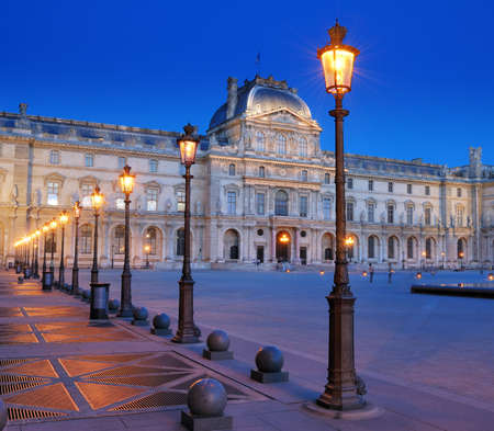 lamppost: Street lanterns in front of the Louvre museum in Paris, France. Editorial
