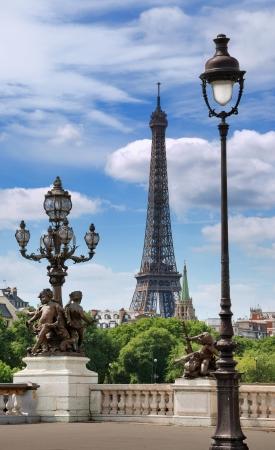 paris street: Street lanterns on the bridge Alexandre III and the Eiffel tower in Paris, France.