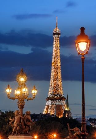 Straßenlaternen auf der Brücke Alexandre III und Eiffelturm am Abend in Paris, Frankreich. Am Anfang jeder Stunde am Eiffelturm Licht-Show von 20.000 Glühbirnen angeordnet. Standard-Bild - 15347065