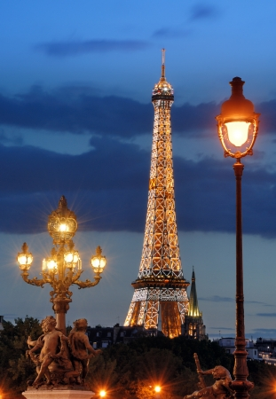 Street lanterns on the bridge Alexandre III and the Eiffel tower in the evening in Paris, France. In the beginning of each hour on Eiffel Tower is arranged light show by 20,000 light bulbs.