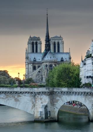 notre dame de paris: The Notre Dame de Paris and Pont de la Tournelle, arch bridge across river Seine in Paris, France.