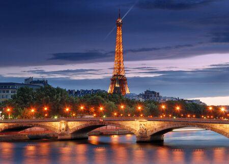 seine: De verlichte Eiffeltoren en de brug Pont des Invalides in Parijs, Frankrijk. Stockfoto