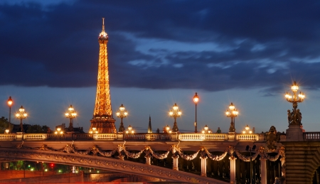 The illuminated Eiffel Tower and Pont Alexandre III in Paris, France. Editorial