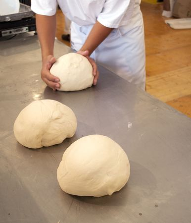 Baker hands preparing three doughs on the counter