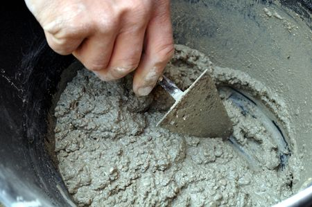mason: Detail of mason hand preparing cement Stock Photo