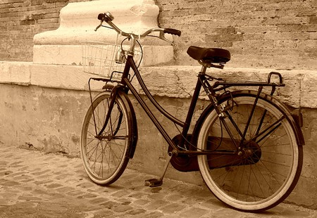 Vintage Bicycle leaning on a wall in italian street photo