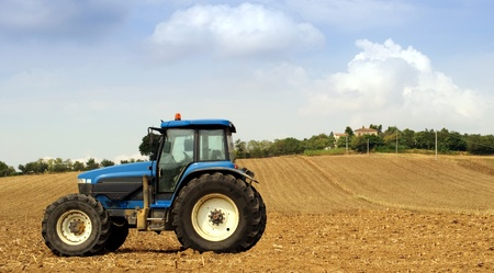 Tractor in a field, agricultural scene in summer Stock Photo