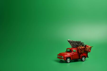 Red pickup truck with a Christmas tree in the back on an isolated green background. Minimal christmas concept. Copy space, banner, decoration. Stock Photo