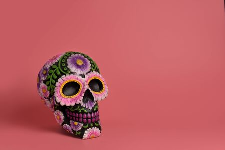 The black skull is decorated with purple and pink flowers. Da de los Muertos Hallovin project. The skull is isolated on a pink background and is located laterally. Copy space, postcard, banner, holiday concept. Banco de Imagens