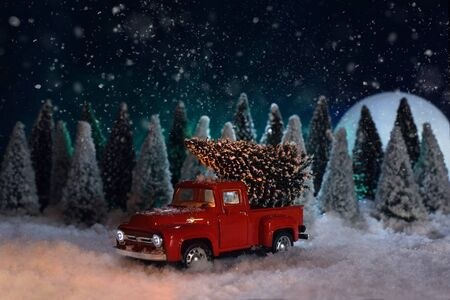 A toy red Chevrolet pickup truck carries a Christmas tree in the forest.