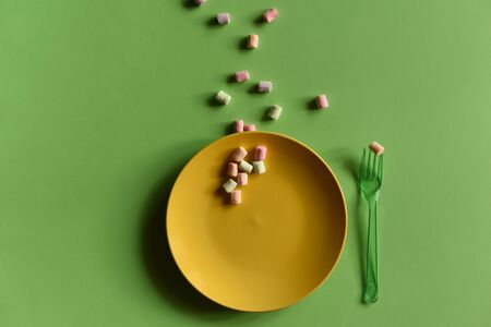 An empty yellow plate on a green background. Multicolored marshmallows are spread around. mosk-up. Banner, postcard, copy space, concept photography