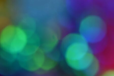 Multicolor large round bright bokeh. Multicolor large round bright bokeh. Clear green balls in the foreground, background blurred in blue, yellow and purple.