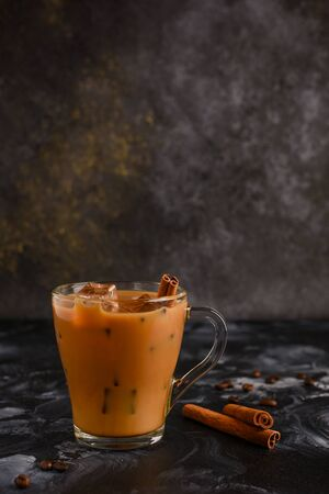 Iced coffee with milk on a dark background with Cinnamon stick and ice cubes.
