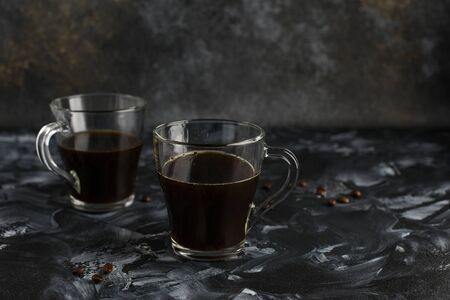 Two glass mugs of black freshly brewed coffee. Transparent cups on a dark background with coffee beans. Side view. Copy space Reklamní fotografie