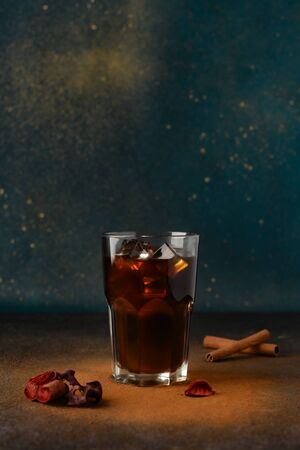 Iced black coffee in a tall glass glass with ice cubes. Cinnamon is scattered around and two sticks of cinnamon in the background. Copy space