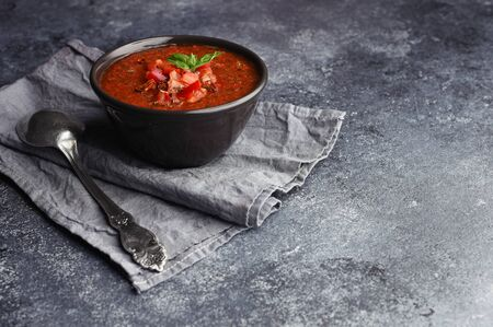 Bowl of homemade gazpacho soup. Vintage spoon on grey towel next to bowl with cold spicy tomato soup. Copy space on textured grey stone desk. Zdjęcie Seryjne
