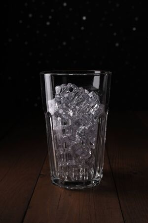 Ice cubes in tall transparent glass on a wooden table. The light illuminates the glass with ice showing the testure. Dark background with silver bokeh.