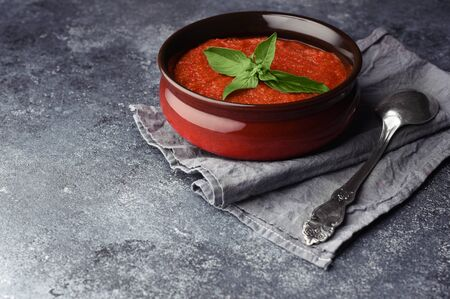 Traditional Spanish cold summer soup gazpacho. Tomato soup decorated with leaf of basil. Textured stone background with place for text. Soup in bowl with spoon on grey towel.