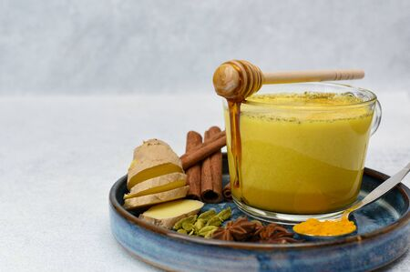 Golden milk or turmeric latte with curcuma powder on light background copy space. Healthy ayurvedic drink. Trendy Indian natural detox beverage with spices for vegans 免版税图像