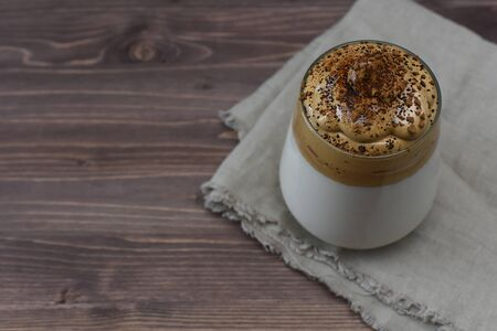 Dalgona coffee on a wooden background with copy space. Homemade dalgona coffee in glass with milk. Trendy fluffy creamy whipped coffee on wooden stand.