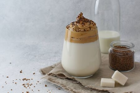 Dalgona coffee, a trendy drink. A glass of Dalgona coffee next to instant coffee, sugar and a bottle of milk. Recipe of homemade Whipped frothy coffee with copy space. 免版税图像