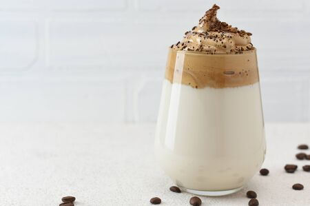 Dalgona coffee in glass decorated with coffee beans. Dalgona Coffee, a trendy fluffy creamy whipped coffee on white background with copy space.