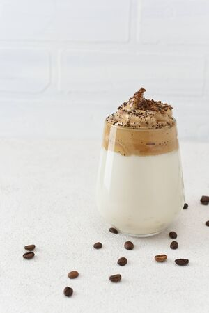 Dalgona coffee in glass with coffee beans around. A trendy fluffy whipped coffee. Latte espresso with coffee foam in glass on white background with copy space.