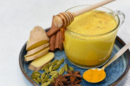 Golden milk in glass cup with spices over close up. Honey flows in a mug.