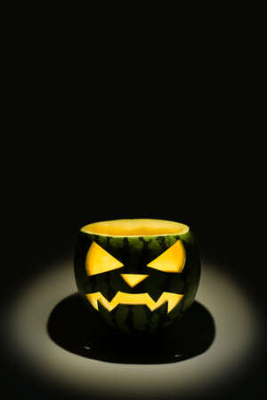 Watermelon carved in the style of Halloween pumpkin. Halloween watermelon glows in the dark. Black background with copy space. Foto de archivo