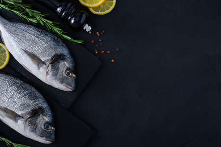 Fresh raw dorado fish on black stone background with spices, rosemary and lemon. Culinary seafood background with copy space. Two Dorada fishes on shale boards.