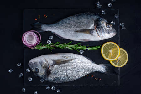 Raw Dorado lie on a black stone chopping Board on a dark concrete table. Top view of fresh Dorada fishes with lemon, rosemary, onion, pepperoni ice.