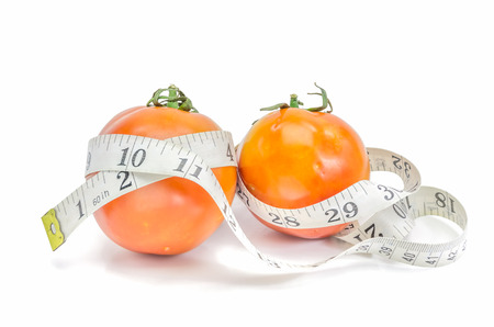 skiny: Live Healthy - fresh tomato with measuring tape on white background. Stock Photo