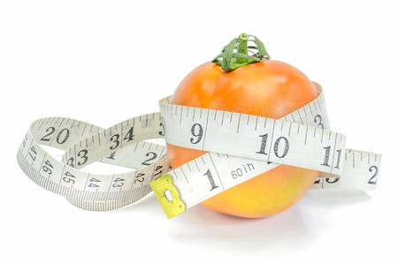 Live Healthy - fresh tomato with measuring tape on white background. Stock Photo