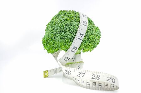 Live Healthy - Fresh raw broccoli with measuring tape on white background. Stock Photo