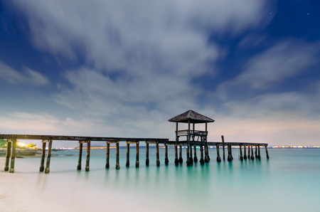 wide  wet: Beautiful morning light of wooden landing with pavilion in the sea at black sand beach, Rayong, Province of Thailand. Stock Photo