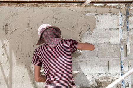 gloved: Close up of industrial bricklayer installing cement on construction site Stock Photo