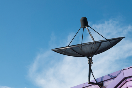 satelite: Black satellite dish antennas on blue sky.