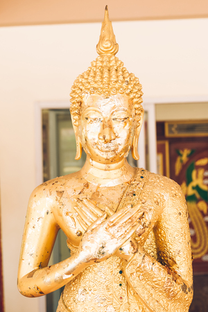 Golden Buddha statue in Buddhist temple or wat, is public domain or treasure of Buddhism.