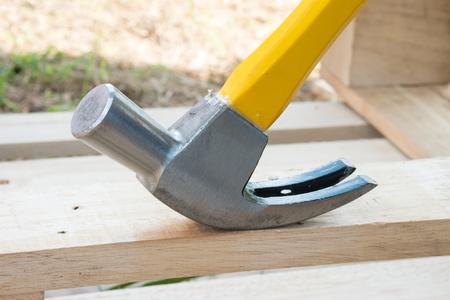 Yellow hammer and Nail Using hammer and nail on wood.