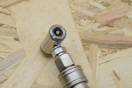 Air coupling connector, Pneumatic fitting on wood background.