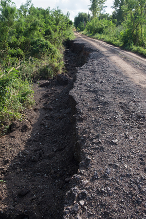 Old road. Concept road in huge pits. Symbol of hard way. Massive Cracks in road after Earthquake