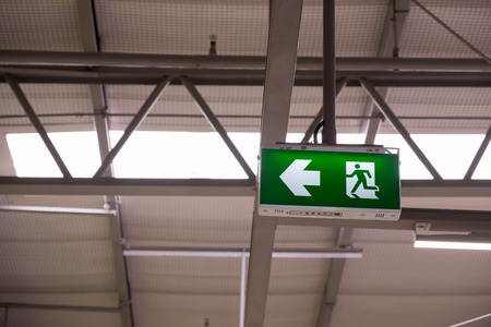 Fire exit light sign. Green emergency exit sign showing the way to escape. Standard-Bild