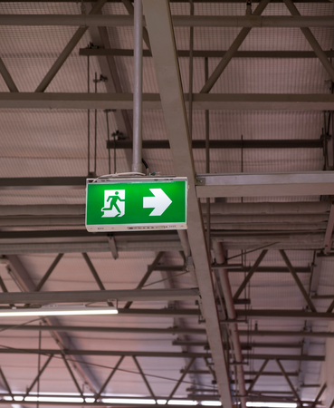 Fire exit light sign. Green emergency exit sign showing the way to escape. Banque d'images