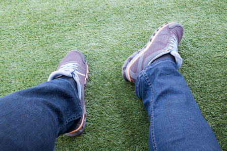 Male sneaker out of torn jeans on a green artificial grass football field. 免版税图像