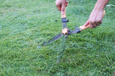 Gardener scissors on the grassy background. Gardening concept background.
