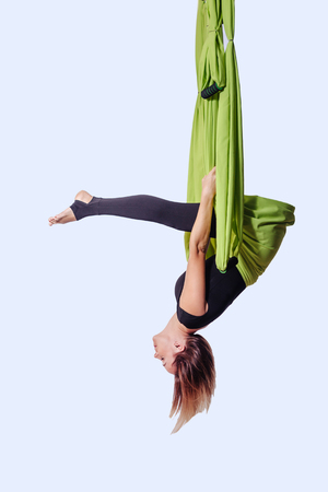 Young woman doing aerial yoga in green hammock.