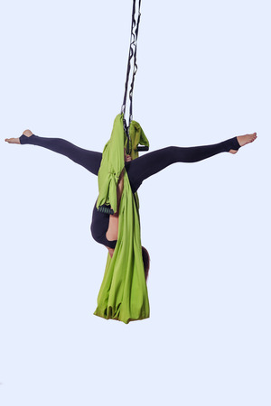 Young woman doing anti-gravity aerial yoga in hammock on a light gray isolated background.