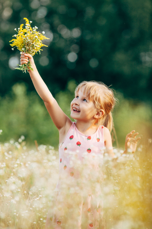 Sweet little girl in a meadow with wild spring flowers Stock Photo