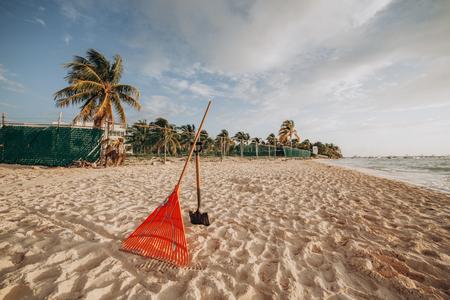 Herramientas para la limpieza de la playa. Rastrillo y pala sobre arena
