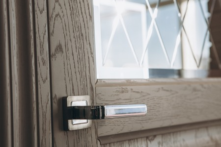 Modern style door handle on wooden door